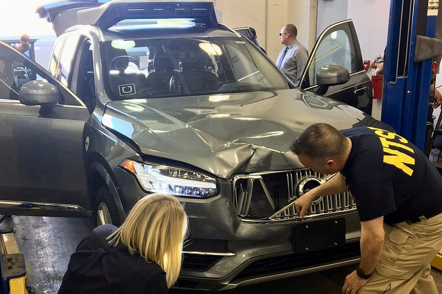 US National Transportation Safety Board (NTSB) investigators examine a self-driving Uber vehicle involved in a fatal accident in Tempe, Arizona, US, on March 20, 2018.