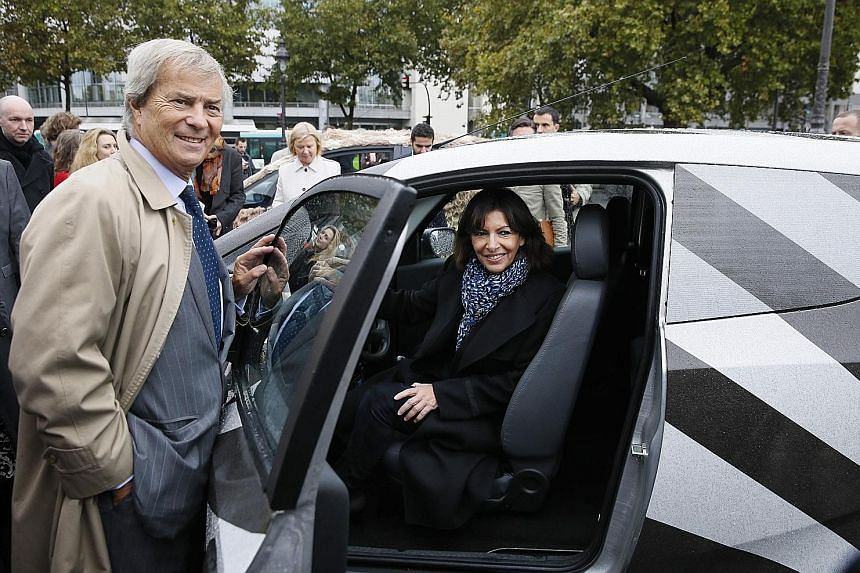 """A flyer reading """"The end of Autolib! Why such a hasty rupture and in what interest?"""" at an Autolib charging station in Paris last Thursday. Mayor of Paris Anne Hidalgo and Mr Vincent Bollore, head of the Bollore Group, posing with an Autolib car in 2"""