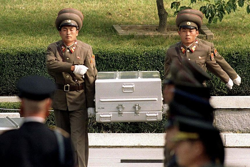 North Korean soldiers carrying a coffin believed to contain the remains of a US soldier to the border with South Korea in 1998. The US is preparing to receive more remains of troops missing in action during the Korean War in coming days.