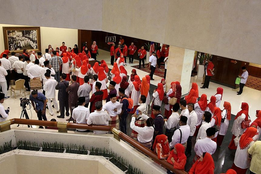 Delegates from Umno's Subang division in line to cast their votes yesterday. Delegates from over 20,000 party branches voted to decide who will lead the Malay nationalist party's Youth, Wanita and Puteri wings.
