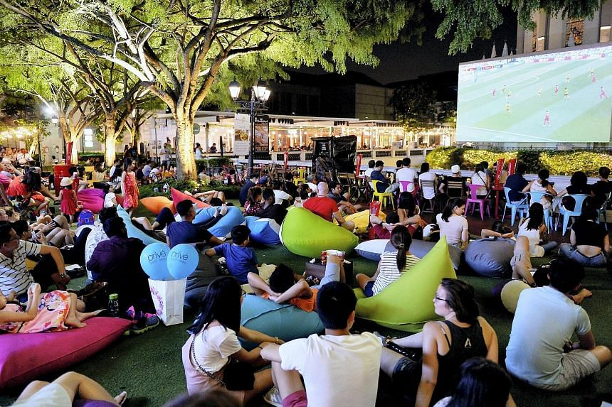 Football fans watching the World Cup match between Belgium and Tunisia at Chijmes last night. With the drama of the knockout rounds fast approaching, bigger crowds are expected at screening locations islandwide.