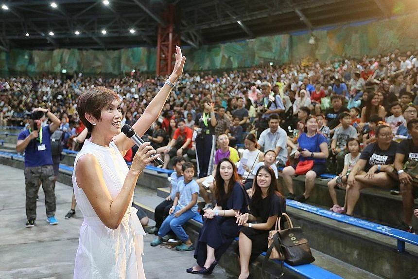 HomeTeamNS president Josephine Teo, who is Manpower Minister, speaking to some 5,000 HomeTeamNS members, volunteers and their families at the inaugural family day event at Universal Studios yesterday.