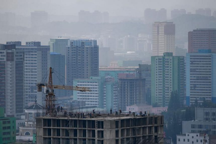 Workers on top of a new construction in front of the skyline of Pyongyang, North Korea, on June 12, 2018.