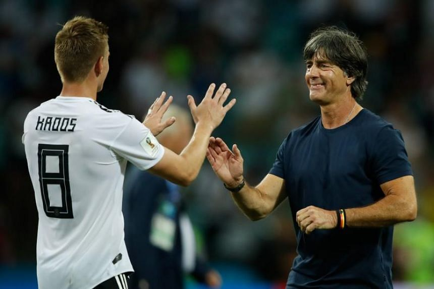 Germany's midfielder Toni Kroos (left) is congratulated by Germany's coach Joachim Low at the end of the Russia 2018 World Cup Group F football match between Germany and Sweden at the Fisht Stadium in Sochi on June 23, 2018.