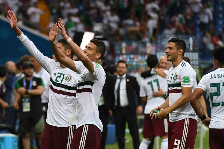 Mexico's defender Edson Alvarez (left) and Mexico's forward Raul Jimenez (second from left) wave to the crowd after the final whistle of the Russia 2018 World Cup Group F football match between South Korea and Mexico at the Rostov Arena in Rostov-On-