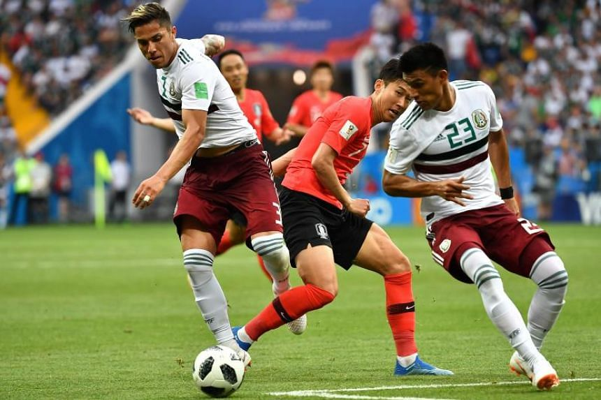 South Korea's forward Son Heung-min (centre) fights for the ball with Mexico's defender Carlos Salcedo (left) and Mexico's defender Jesus Gallardo during the Russia 2018 World Cup Group F football match between South Korea and Mexico at the Rostov Ar