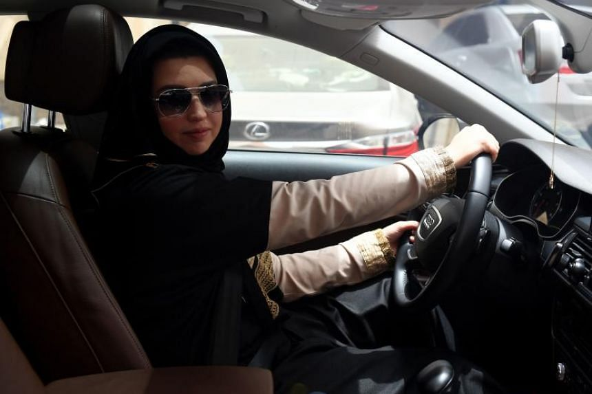 Daniah al-Ghalbi, a newly-licensed Saudi woman driver, sits in her car during a test-drive in the Red Sea resort of Jeddah on June 23, 2018