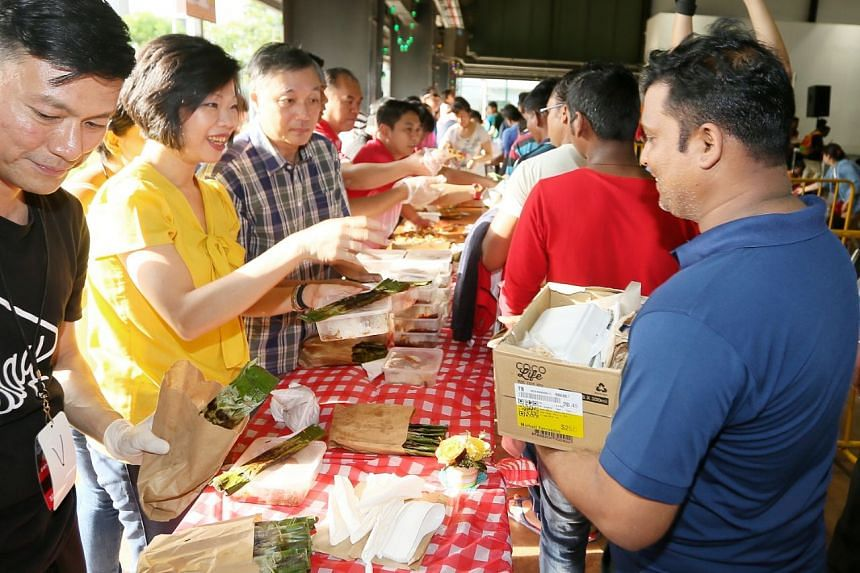 Senior Minister of State Sim Ann and other volunteers handing out food to workers.