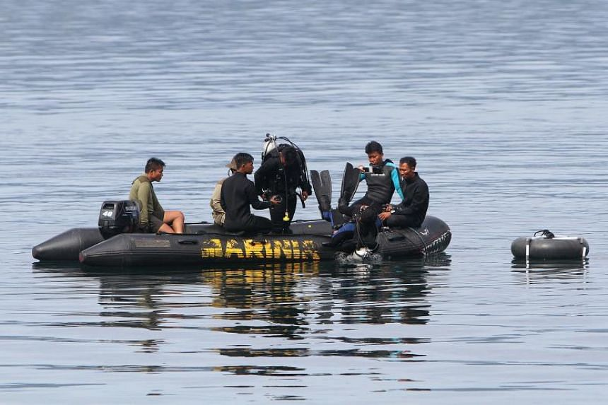 Divers conducting search and retrieval operations in Lake Toba after a ferry capsized and sank, on June 24, 2018.