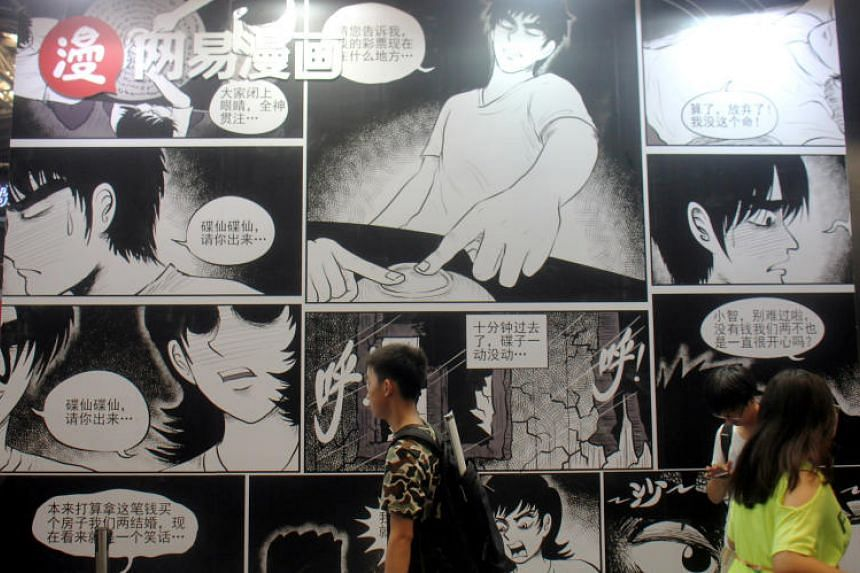 People walking past the NetEase Comics booth at the China International Cartoon and Game Expo in Shanghai on July 6, 2017.