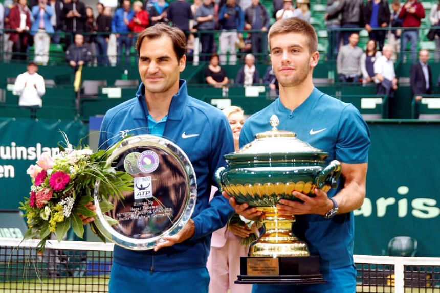 Borna Coric (right) posing with his trophy alongside runner-up Roger Federer after winning the Halle Open on June 24, 2018.
