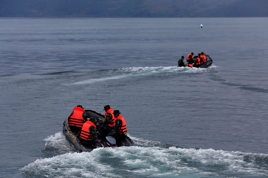 Rescue crew using rubber boats during a search operation for missing passengers on June 23, 2018, after a ferry sank earlier in the week in Lake Toba in North Sumatra, Indonesia, .