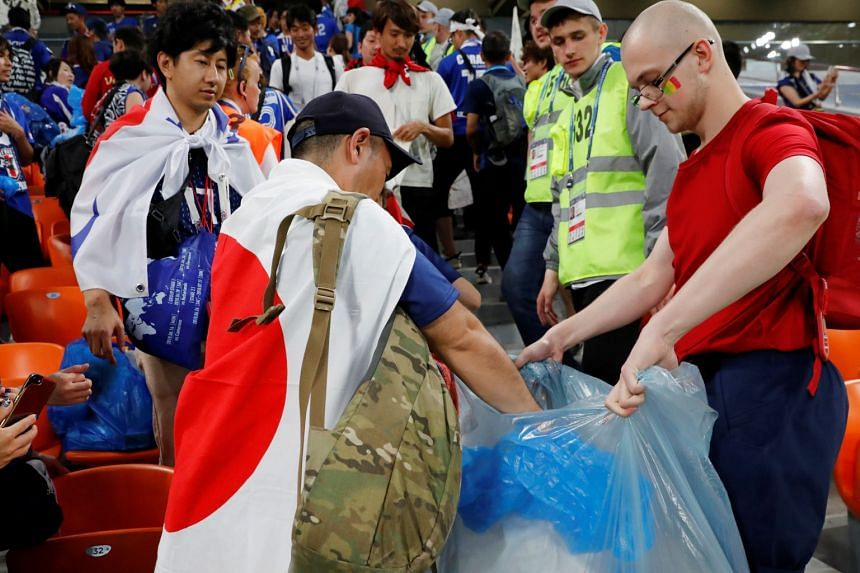 Japanese fans clean up the stadium after the match between Japan and Senegal, on June 24, 2018.