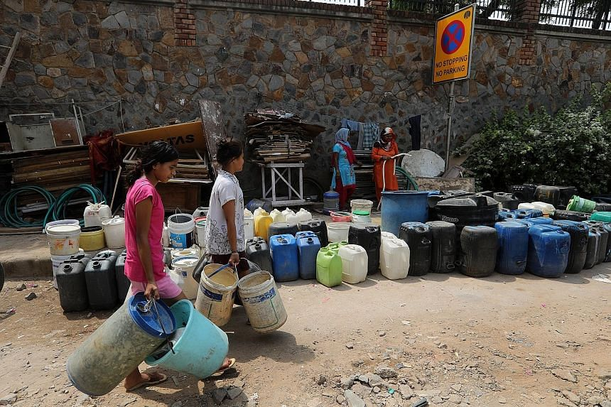 People waiting to fill up containers with water from a tanker in Sanjay camp in New Delhi on Saturday. According to government think-tank Niti Aayog, demand for water will be twice the available supply by 2030. Water scarcity may also account for a 6