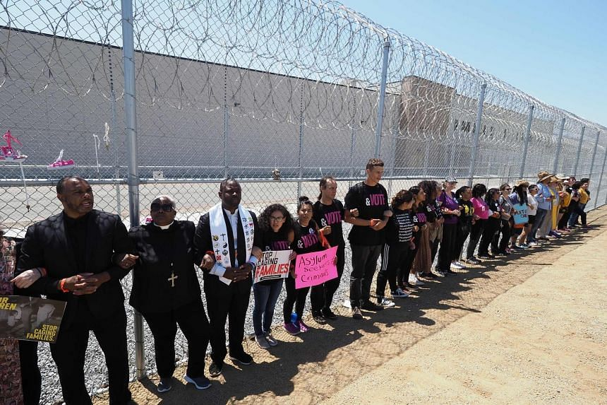 Protesters linking arms after they tied children's shoes and keys to the fence outside the Otay Mesa Detention Centre, near San Diego, at a demonstration last Saturday. Hundreds of protesters rallied in solidarity with people being held inside the ce