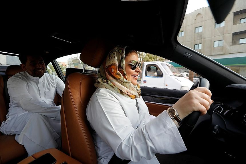 Psychologist Samira al-Ghamdi, 47, driving to work yesterday in Jeddah, as her son Abdulmalik, 26, sat in the back seat, as the world's last ban on female drivers was lifted.