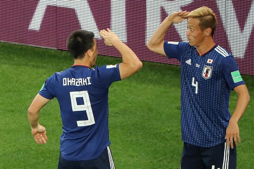 Japan's veteran forward Keisuke Honda (far right) celebrating with Shinji Okazaki after scoring their second goal against Senegal in their 2-2 draw last night. Takashi Inui had scored their first equaliser in the 34th minute. Senegal took the lead tw