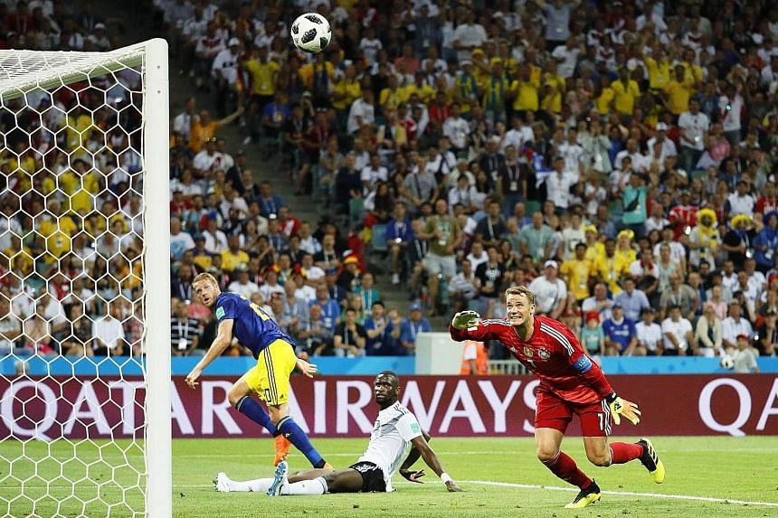 Sweden's goalkeeper Robin Olsen (above) fails to stop Toni Kroos' free kick deep into stoppage time in Saturday's match, which Germany won 2-1. Germany's defensive frailties being exposed, with Ola Toivonen (far left) running in between two opponents