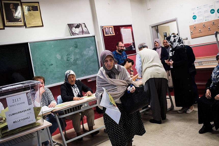 A woman holding ballot papers and a stamp before voting in twin Turkish presidential and parliamentary elections in Istanbul yesterday. Over 56 million eligible voters were for the first time casting ballots in both elections.