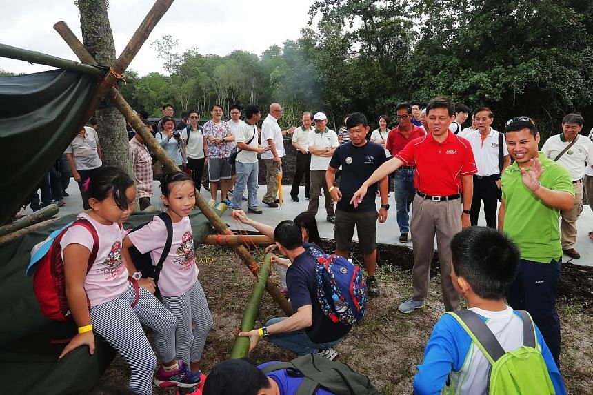 Minister for Social and Family Development Desmond Lee (in green shirt) and Trade and Industry Minister Chan Chun Sing touring the Ubin Living Lab, which supports field studies and environmental education on the island, yesterday.