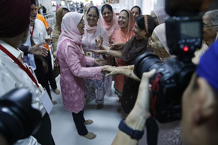 President Halimah Yacob being greeted by members of the Sikh community yesterday during Sri Guru Singh Sabha Singapore's 100th anniversary celebrations.