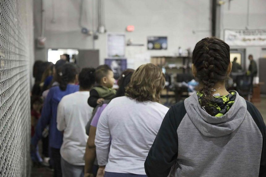 Illegal border crossers into the US being detained by US Border Patrol agents at a processing centre in McAllen, Texas.