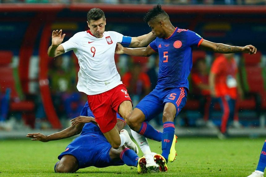 Poland's forward Robert Lewandowski (centre) fights for the ball with Colombia's defender Yerry Mina (left) and Colombia's midfielder Wilmar Barrios during match between Poland and Colombia at the Kazan Arena, on June 24, 2018.