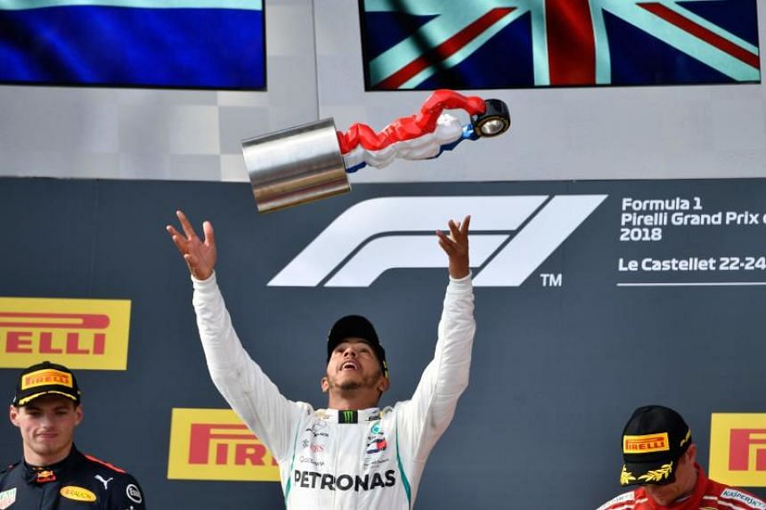Winner Mercedes' British driver Lewis Hamilton (centre) celebrates on the podium next to second placed Red Bull Racing's Dutch driver Max Verstappen (left) and third placed Ferrari's Finnish driver Kimi Raikkonen after the Formula One Grand Prix de F