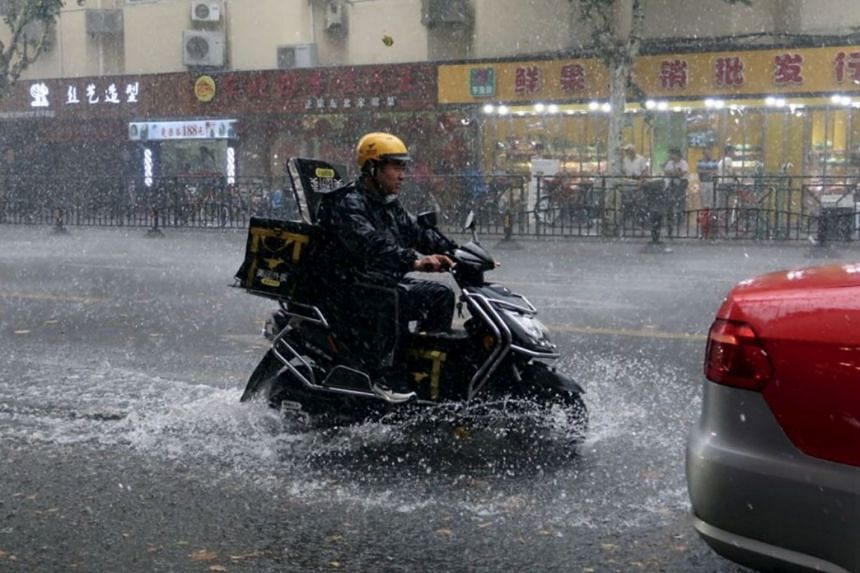 A deliveryman riding through a rainstorm in Shanghai. Many companies that operate via online apps do not offer employment contracts or insurance for workers in the event of sickness or injury.