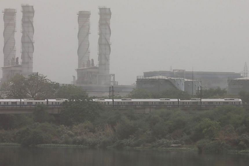File photo showing a train passing by a power plant amid heavy dust and pollution in New Delhi, India, on June 14, 2018. India's industrial sector grew at 4.3 per cent last year but growth slowed from 4.6 per cent a year ago.