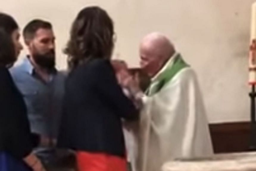 """Gasps could be heard when an 89-year-old priest, after ordering the infant he was holding to """"be quiet"""", sharply slapped his cheek."""