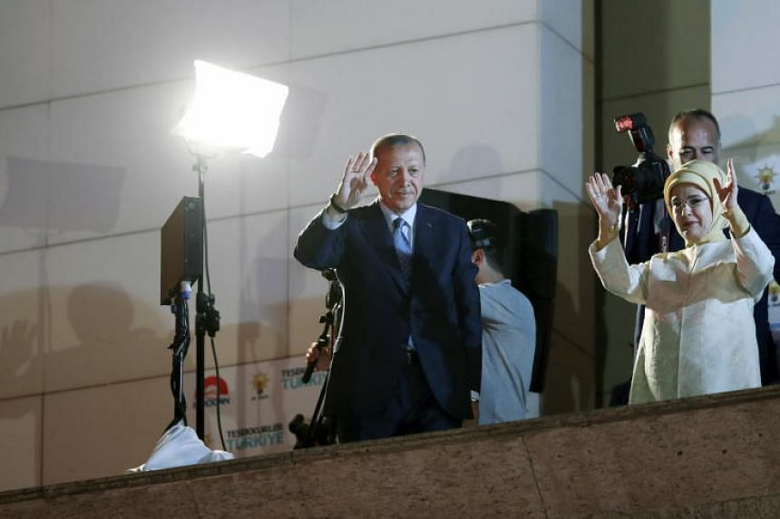 Turkish President Recep Tayyip Erdogan and his wife wave to supporters in Ankara, on June 24, 2018.