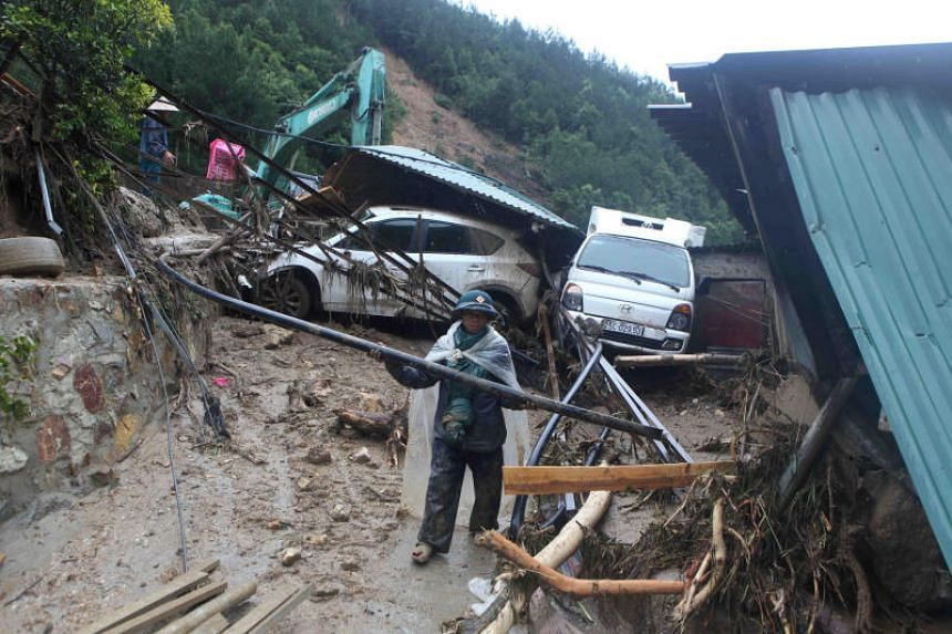 A paramilitary clears debris after a landslide in Vietnam's Lai Chau province, on June 25, 2018.