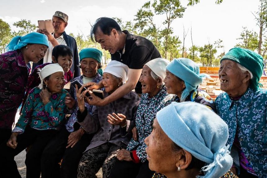 Lu Wenzhen, the local Communist Party chief, talks with residents at the Yugouliang village in Hebei, China, on June 20, 2018.
