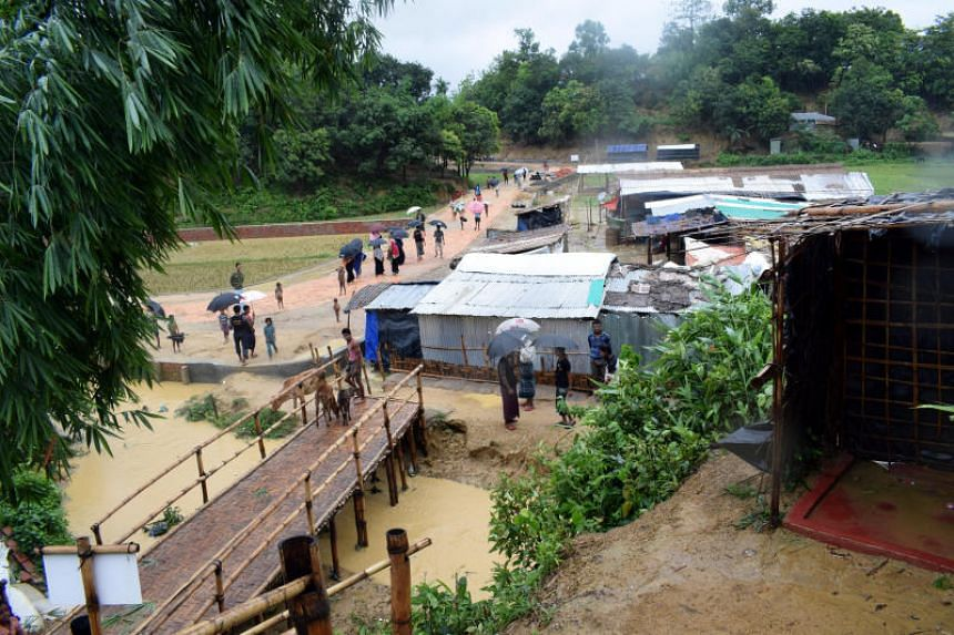 People walking after a storm at Chakmarkul refugee camp where Rohingya Muslims are taking refuge in Cox's Bazar, Bangladesh, on June 10, 2018.