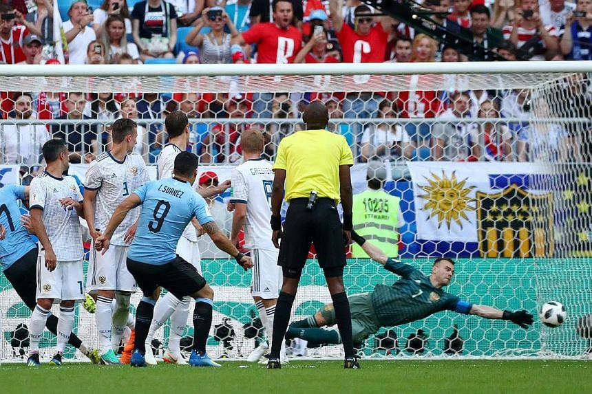 Luis Suarez watching his free kick go beyond the reach of Russia goalkeeper Igor Akinfeev for Uruguay's first goal. The South Americans topped Group A with their 3-0 victory.