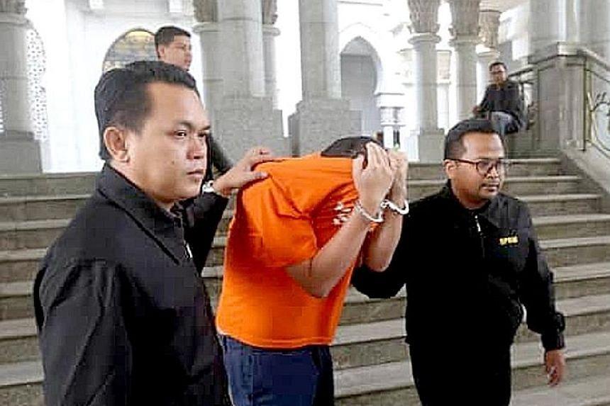 Investigators leading Mr Amhari Efendi Nazaruddin out of the magistrate's court in Putrajaya yesterday.
