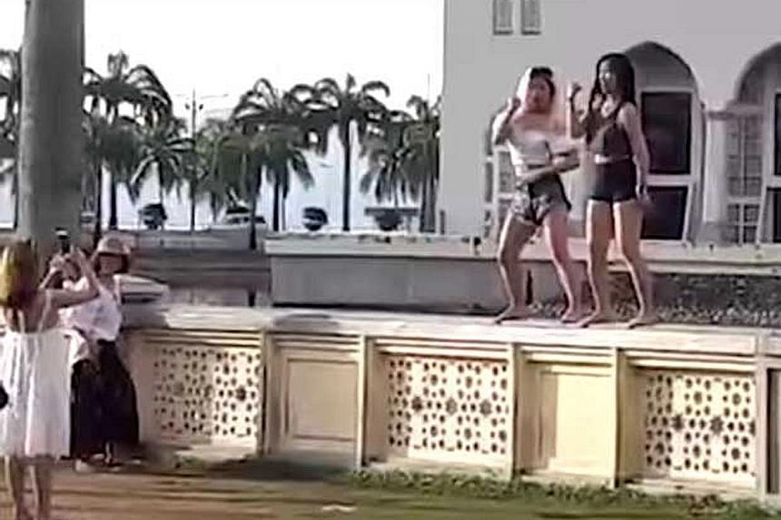 Sabah residents and local Muslim groups are furious over a video of this couple - in skimpy shorts and tops - dancing on a wall outside the main mosque in Kota Kinabalu that has gone viral online.