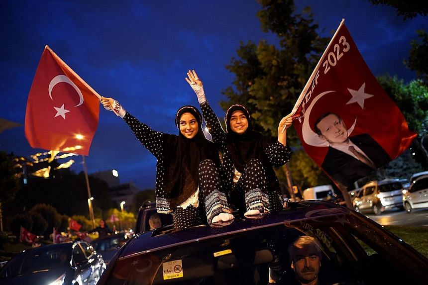 Left: President Recep Tayyip Erdogan greeting his supporters from the balcony of his ruling Justice and Development Party (AKP) headquarters in Ankara, Turkey, on Sunday night. Below left: Supporters waving flags of Mr Erdogan and the AKP outside the