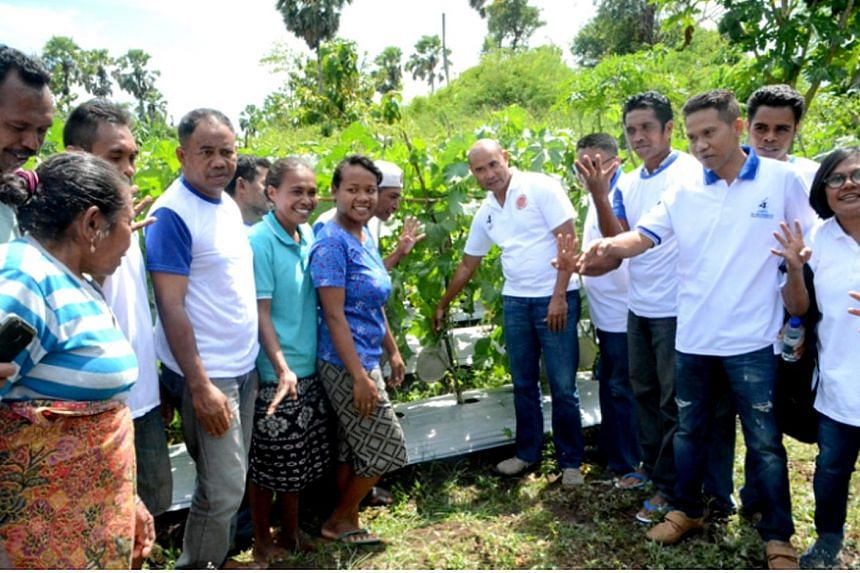 Above: Mr Viktor Laiskodat (centre) with melon farmers in Desa Naioni, East Nusa Tenggara. Left: Mr Benny K. Harman (with green scarf) on the campaign trail. He and his rival Mr Viktor are considered the front runners for the post of governor.