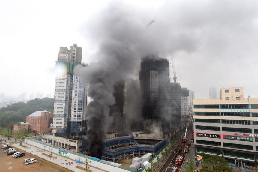Smoke engulfing an apartment building construction site after a fire broke out in the administrative town of Sejong, South Korea, on June 26, 2018.
