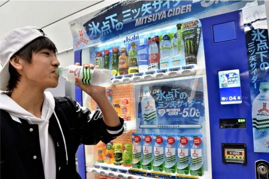 A man drinks Mitsuya Cider from a vending machine that cools beverages to below freezing point.