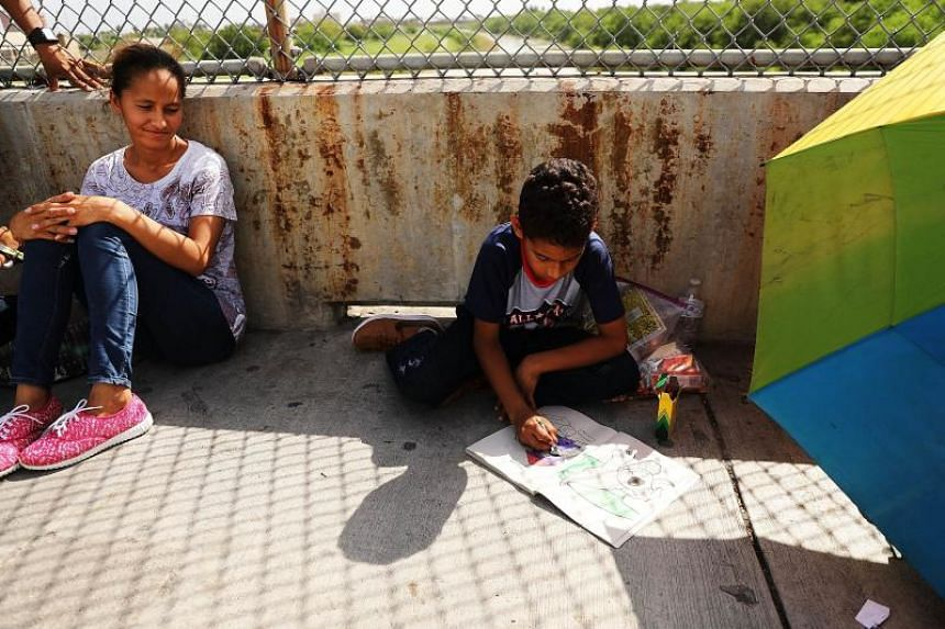 A Honduran child works on a colouring book while waiting with his family along the border bridge in Brownsville, Texas, after being denied entry into the US from Mexico on June 25, 2018.