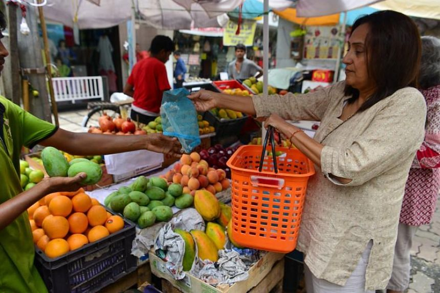 A shopper uses a bag she carried from home to a fruit stall in Mumbai on June 26, 2018, as the city civic authorities try to enforce a ban on single-use plastic bags.