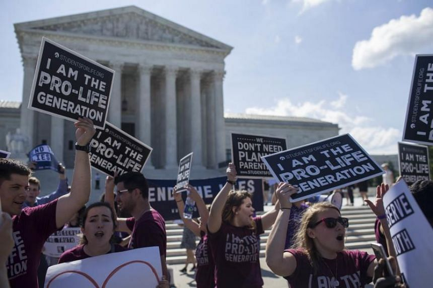 Abortion opponents hold signs in front of the US Supreme Court on June 25, 2018 in Washington, DC.