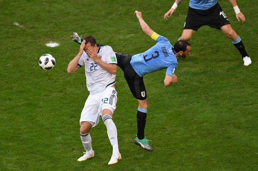 Uruguay's defender Diego Godin (right) challenges Russia's forward Artem Dzyuba during the Russia 2018 World Cup Group A football match between Uruguay and Russia at the Samara Arena in Samara on June 25, 2018.
