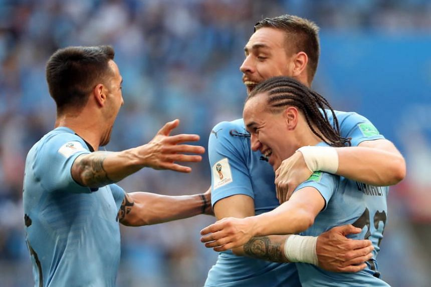 Diego Laxalt of Uruguay (right) celebrates scoring goals with Sebastian Coates of Uruguay (left) and Matias Vecino of Uruguay during the Fifa World Cup 2018 group A preliminary round soccer match between Uruguay and Russia in Samara, Russia, on June