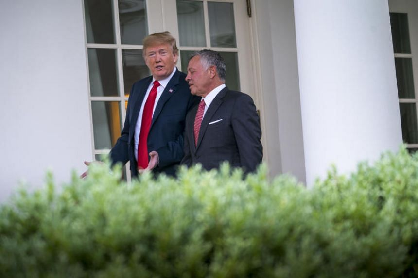 President Donald Trump and King Abdullah II bin Al-Hussein of Jordan speak as they walk to their meeting in the Oval Office of the White House in Washington, on June 25, 2018.