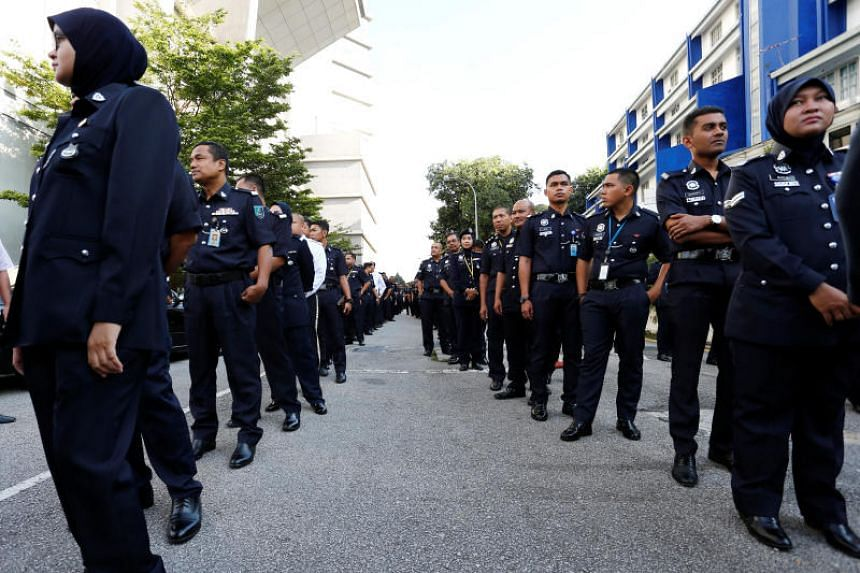 Malaysian police officers line up to vote in the country's 14th general election at the Bukit Aman police headquarters in Kuala Lumpur on May 9, 2018.