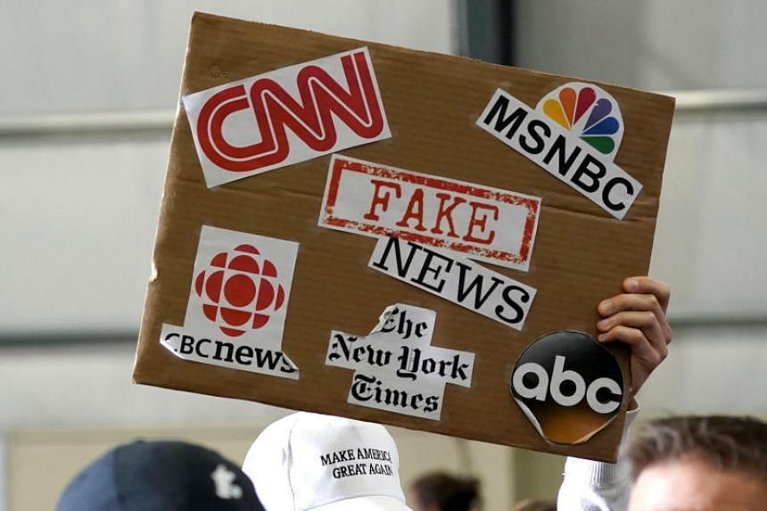 """A sign showing major news organizations along with the words """"fake news"""" is held up as US President Donald Trump speaks at a Make America Great Again Rally in Washington, Michigan on April 28, 2018."""